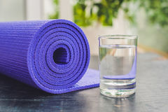 Estera, agua, naranja y mango de la yoga en un fondo de madera Equipo para la yoga Forma de vida, dieta y deporte sanos del conce Foto de archivo