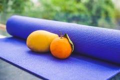 Estera, agua, naranja y mango de la yoga en un fondo de madera Equipo para la yoga Forma de vida, dieta y deporte sanos del conce Imagen de archivo libre de regalías