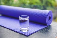 Estera, agua, naranja y mango de la yoga en un fondo de madera Equipo para la yoga Forma de vida, dieta y deporte sanos del conce Imagenes de archivo