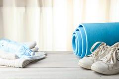 Estera, agua y zapatillas de deporte del gimnasio fotos de archivo libres de regalías