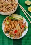 Estera con los tallarines de arroz cortos, la carne y el arroz frito Foto de archivo