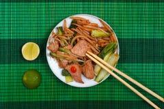 Estera con los tallarines y la carne cortos fritos de arroz Fotos de archivo libres de regalías
