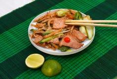Estera con los tallarines y la carne cortos fritos de arroz Imagen de archivo libre de regalías