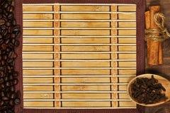 Estera de bambú con el marco de los granos de café y de los condimentos Foto de archivo