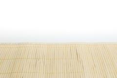 Estera de bambú de Brown en la tabla de cocina blanca Imagenes de archivo