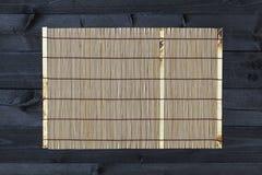 Estera de bambú en la tabla de madera, visión superior fotografía de archivo