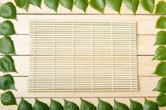 Estera de bambú, opinión superior, sobre un fondo de madera, enmarcado con las hojas de un árbol Fotografía de archivo libre de regalías