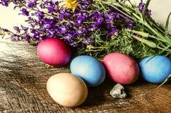 Estera de la paja con los huevos de Pascua coloreados y un ramo de wildflowers púrpuras Imagen de archivo libre de regalías