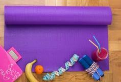 Estera de la yoga con el equipo de deporte en piso Imágenes de archivo libres de regalías