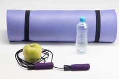 Estera de la yoga con la cuerda que salta, botella de agua, ABS Imagen de archivo