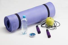 Estera de la yoga con la cuerda que salta, botella de agua, ABS Imágenes de archivo libres de regalías
