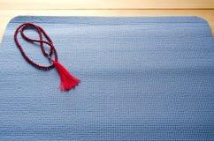 Estera de la yoga con las gotas del mala Fotos de archivo libres de regalías