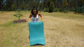 Estera de la yoga de la mujer que se desenrolla latina joven en el parque Imagen de archivo