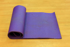 Estera de la yoga en el fondo de madera Fotografía de archivo