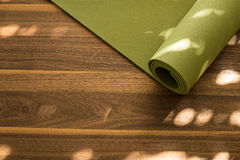 Estera de la yoga en un fondo de madera Imágenes de archivo libres de regalías