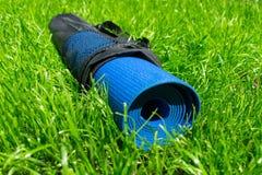 Estera de la yoga en una cubierta en hierba verde, el concepto de entrenamiento y la reconstrucci?n foto de archivo