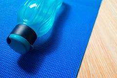 Estera de la yoga y una botella de agua imágenes de archivo libres de regalías