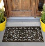 Estera de puerta de goma negra de Mat Indoor Outdoor del piso del raspador fuera del hogar con las flores y las hojas amarillas fotografía de archivo libre de regalías