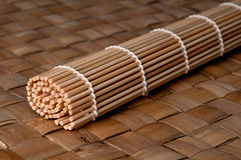 Estera del balanceo del sushi en una estera de lugar de bambú Fotografía de archivo