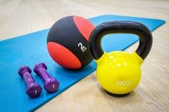 Estera para la aptitud con pesas de gimnasia, peso y la bola Foto de archivo libre de regalías