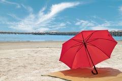Estera roja del paraguas y del bambú en la playa Imágenes de archivo libres de regalías