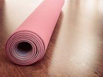 Estera rosada de los pilates, de la yoga o de la aptitud en piso de madera Foto de archivo