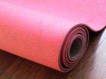 Estera rosada de los pilates, de la yoga o de la aptitud en piso de madera Imagen de archivo libre de regalías