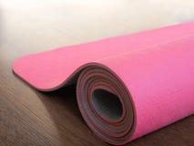 Estera rosada de los pilates, de la yoga o de la aptitud en piso de madera Foto de archivo libre de regalías