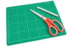 Estera verde del corte con el cortador y las tijeras en el fondo blanco Fotografía de archivo libre de regalías