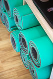 Esteras de la yoga enrolladas en un estante Foto de archivo libre de regalías