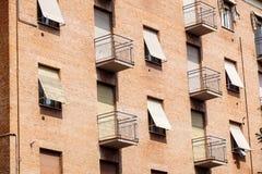 Esterno del blocchetto urbano dell'alloggio del vecchio mattone con gli appartamenti ed il balcone Immagini Stock