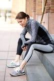Esterno di seduta della donna sportiva che riposa dopo l'allenamento Immagini Stock Libere da Diritti
