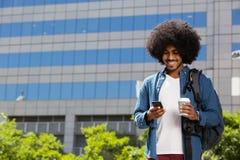 Esterno diritto del giovane uomo di colore con il telefono cellulare e la borsa Immagine Stock