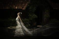 Esterno diritto della bella sposa con il velo che soffia nel vento Immagini Stock