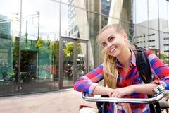 Esterno diritto sorridente della giovane donna con la bici Fotografia Stock