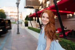 Esterno diritto sorridente della ragazza della testarossa su una via della città Fotografia Stock