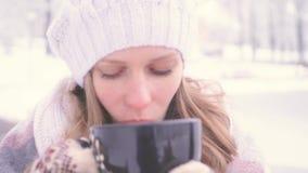 Esterno ouenjoy bevente della cioccolata calda della bella ragazza nell'odore del parco buon e che tiene concetto caldo di comodi stock footage