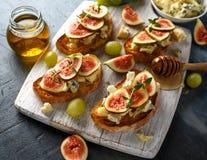 Estes tartines do figo e do Gorgonzola, brinde, bruschetta chuviscado com mel na placa de madeira branca imagem de stock royalty free