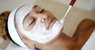 Esteticista que aplica a máscara facial imagens de stock royalty free