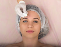 Esteticista que examina a cara de um cliente fêmea novo no salão de beleza dos termas o esteticista remove a máscara protetora do Imagem de Stock Royalty Free