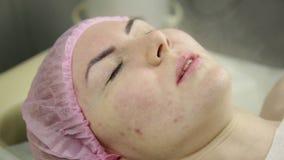 Esteticista que faz o procedimento de limpeza do vapor da cara termas, cosmetologia profissional vídeos de arquivo