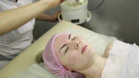Esteticista que faz o procedimento de limpeza do vapor da cara termas, cosmetologia profissional filme