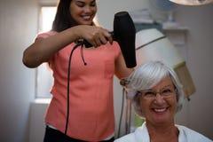 Esteticista que seca o cabelo superior da mulher foto de stock
