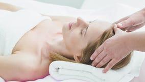 Estetista abile che massaggia la testa della femmina al salone archivi video