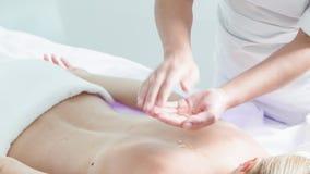 Estetista abile che prepara corpo umano per il massaggio archivi video