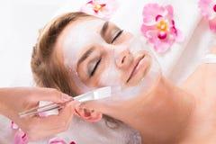 Estetista Applying Mask On Customer& x27; fronte di s al salone Fotografia Stock