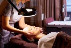 Estetista che fa massaggio di fronte alla donna alla stazione termale Fotografia Stock