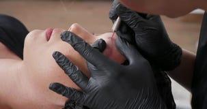 Estetista che lavora duro per rimuovere il vecchio tatuaggio dalla pelle del sopracciglio stock footage