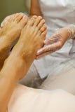 Estetista che prende cura del piede del cliente femminile che dà trattamento di pedicure Immagine Stock