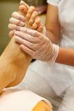 Estetista che prende la cura del piede del cliente femminile che dà il pedicure - passi il massaggio con sfregano Immagine Stock